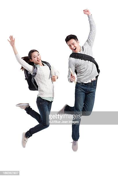 Excited college couple jumping in mid-air