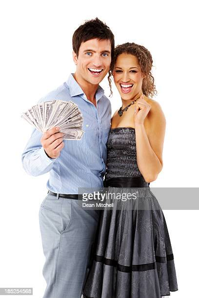 Excited couple holding money isolated over white