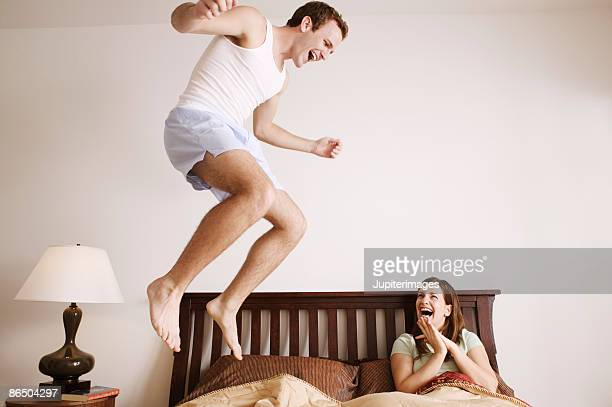 Excited couple jumping on bed