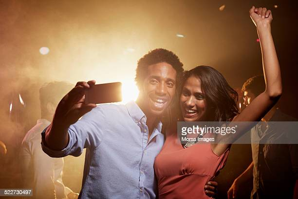 Excited couple taking self portrait in nightclub