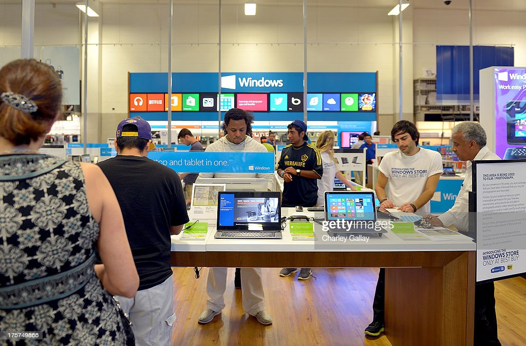 Excited customers check out the latest Windows 8 tech from Microsoft at the grand opening celebration of the new Windows Store Only at Best Buy on...