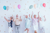Excited elderly men and women having fun at a birthday party with colorful balloons