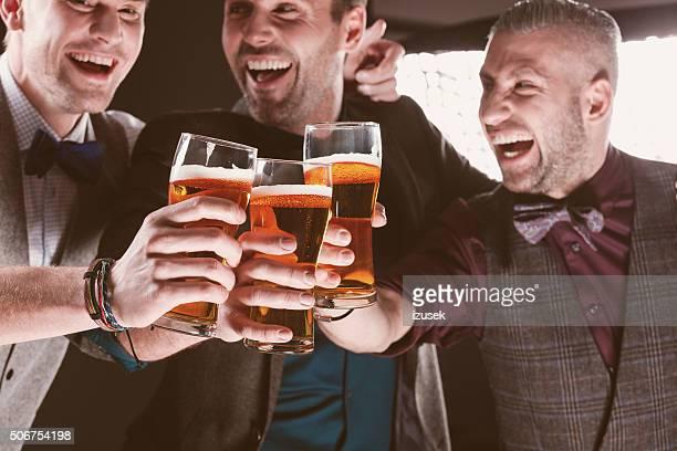 興奮エレガントなビジネスマンにビールで乾杯するナイトクラブ。