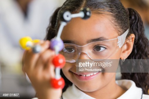 Excited elementary school student using atom model in science class
