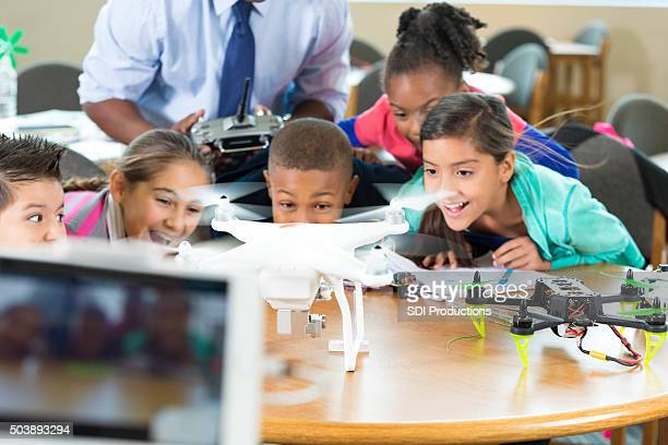Excited elementary students learning to use drone in class