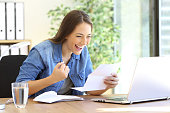 Excited casual entrepreneur girl reading good news in a letter in a desktop at office