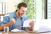 Casual excited entrepreneur reading a letter with good news in a desktop at workplace