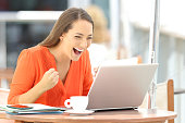 Single excited entrepreneur receiving good news on line in a laptop sitting in a restaurant terrace