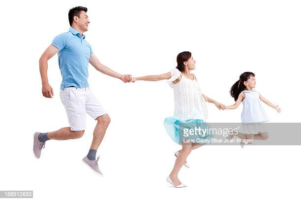 Excited family jumping, hand in hand