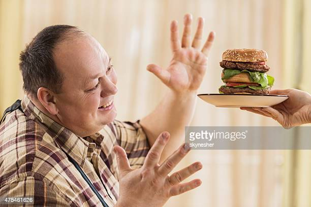 Excited fat man about to eat big hamburger.