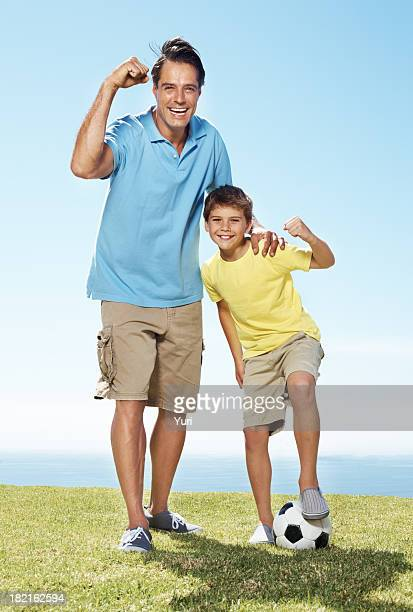 Excited father and son standing outside with a football