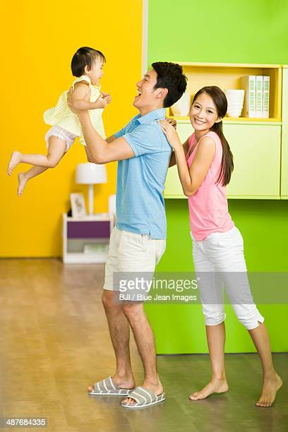 Excited father lifting little daughter up