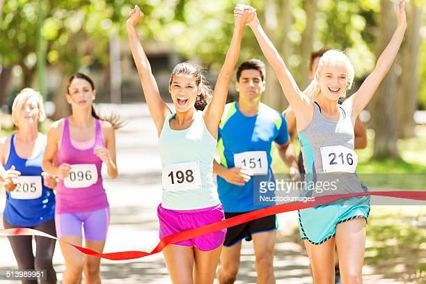 Excited Female Marathon Runners Crossing Finishing Line