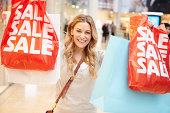 Excited Female Shopper With Sale Bags In Mall Smiling To Camera