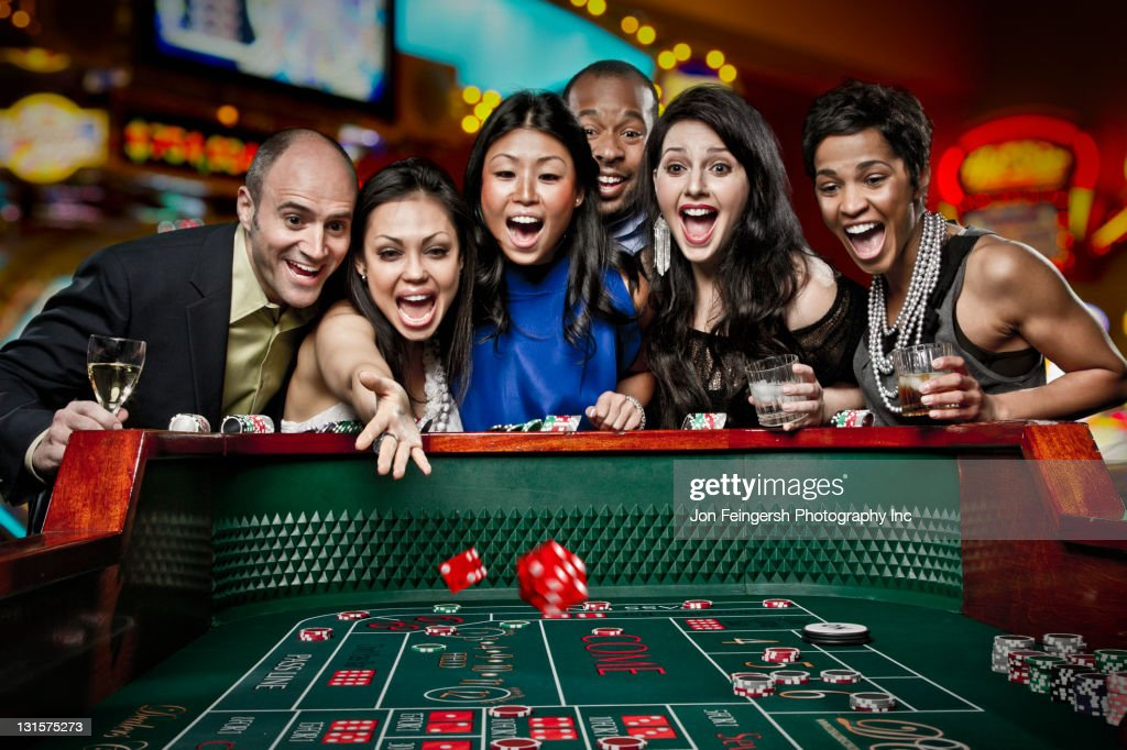 Excited friends gambling at craps table in casino : Stock Photo