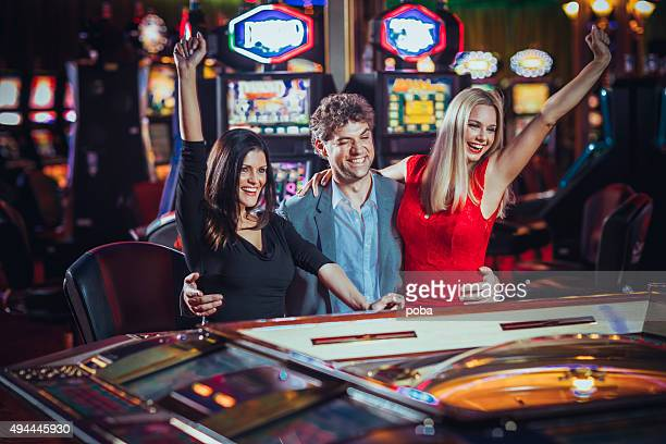 Excited friends   gambling at electronic roulette in casino