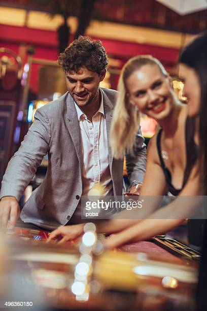 Excited friends   gambling at roulette in casino