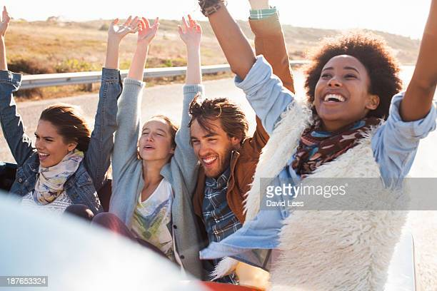 Excited friends in back of truck with arms raised