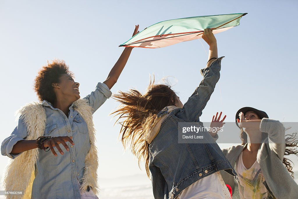 Excited friends playing with kite : Stock Photo