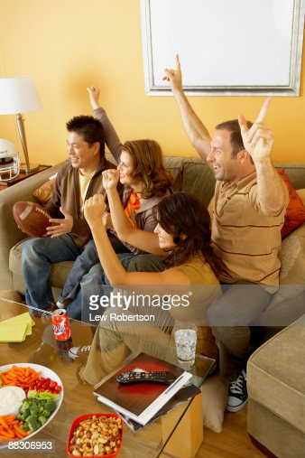 Excited friends watching television together : Stock Photo