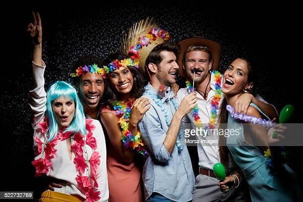 Excited friends wearing garlands in nightclub