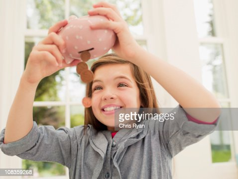 Excited girl emptying coins from piggy bank : Stock Photo