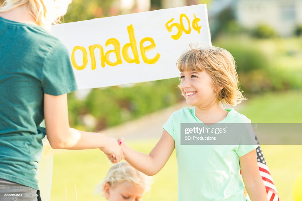 Excited girl getting business at her lemonade stand