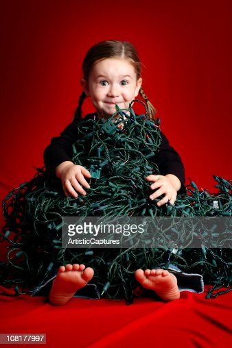 Excited Girl Sitting with Pile of Christmas Lights : Stock Photo