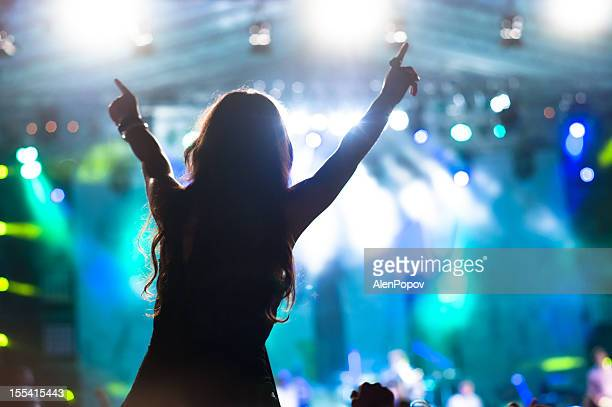 Excited girl stands at concert with blue stage