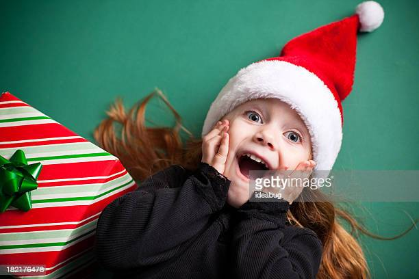 Excited Girl Wearing Santa Hat with Christmas Present