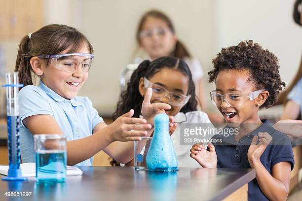 Excited girls using chemistry set together in elementary science classroom