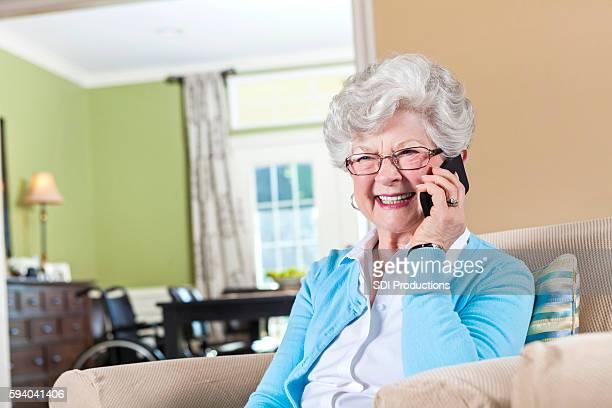 Excited grandma talks on smart phone in living room