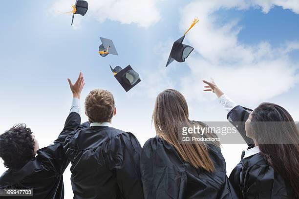Heureux groupe de l'université de diplômés jeter les chapeaux de fête