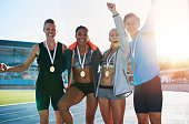 Portrait of ecstatic young athletes together with medals. Group of runners standing together smiling with their hands raised in excitement on racetrack on a bright sunny day.