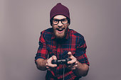Excited happy hipster man playing video game