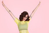 Cheerful woman in trendy clothing and glasses looking happy with hands up on pink background.