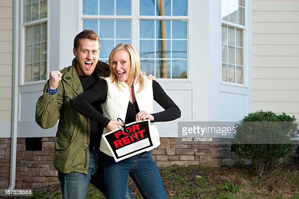 Excited Home Owners Cutting Up For Rent Sign
