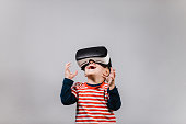 Portrait of cheerful child wearing virtual reality headset against grey background.
