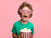 Charming curly boy in glasses holding popcorn and screaming on pink background.