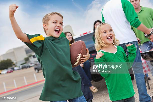 Excited kids tailgating with other fans at college football stadium