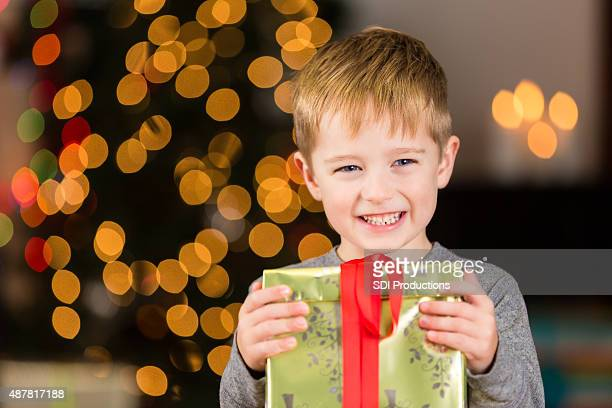 Excited little boy holding Christmas gift near tree