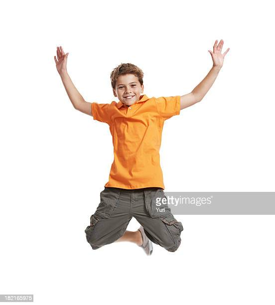 Excited, little boy jumping in mid air on white background