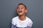 Close up portrait of an excited little boy laughing on gray background