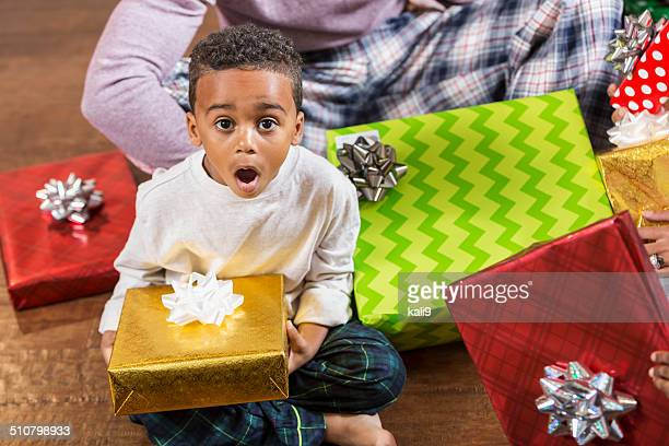 Excited little boy surrounded by Christmas presents