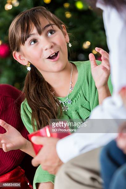 Excited little girl opening Christmas presents with her parents