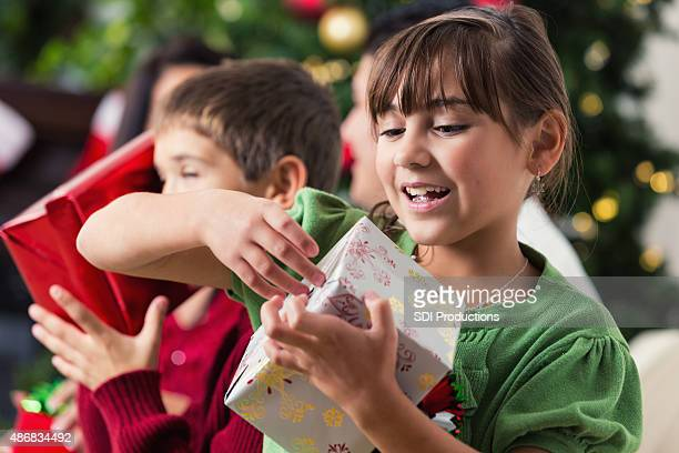 Excited little girl unwrapping Christmas presents with family