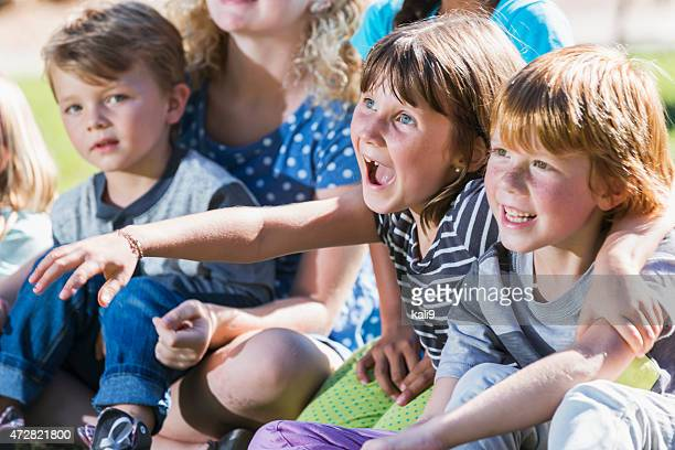 Excited little girl watching something with friends