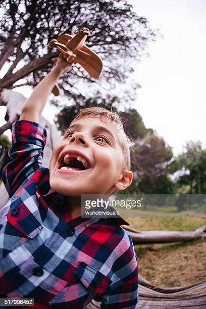 Begeistert kleine Pilot junge Fliegender Holz Spielzeug Flugzeug in Park