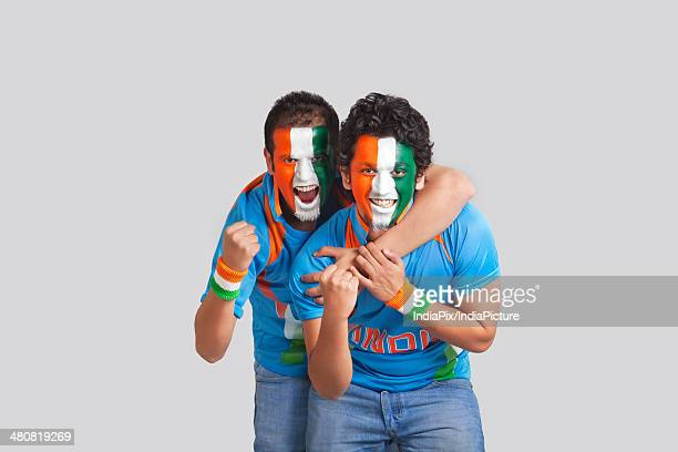 Excited male cricket supporters with face painted in tricolor cheering over gray background