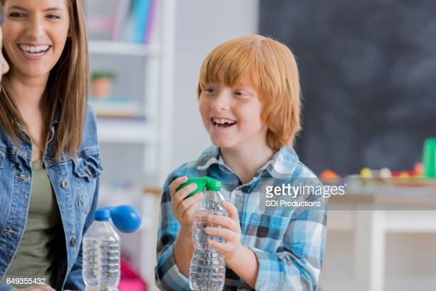 Excited male schoolboy participates in science experiment